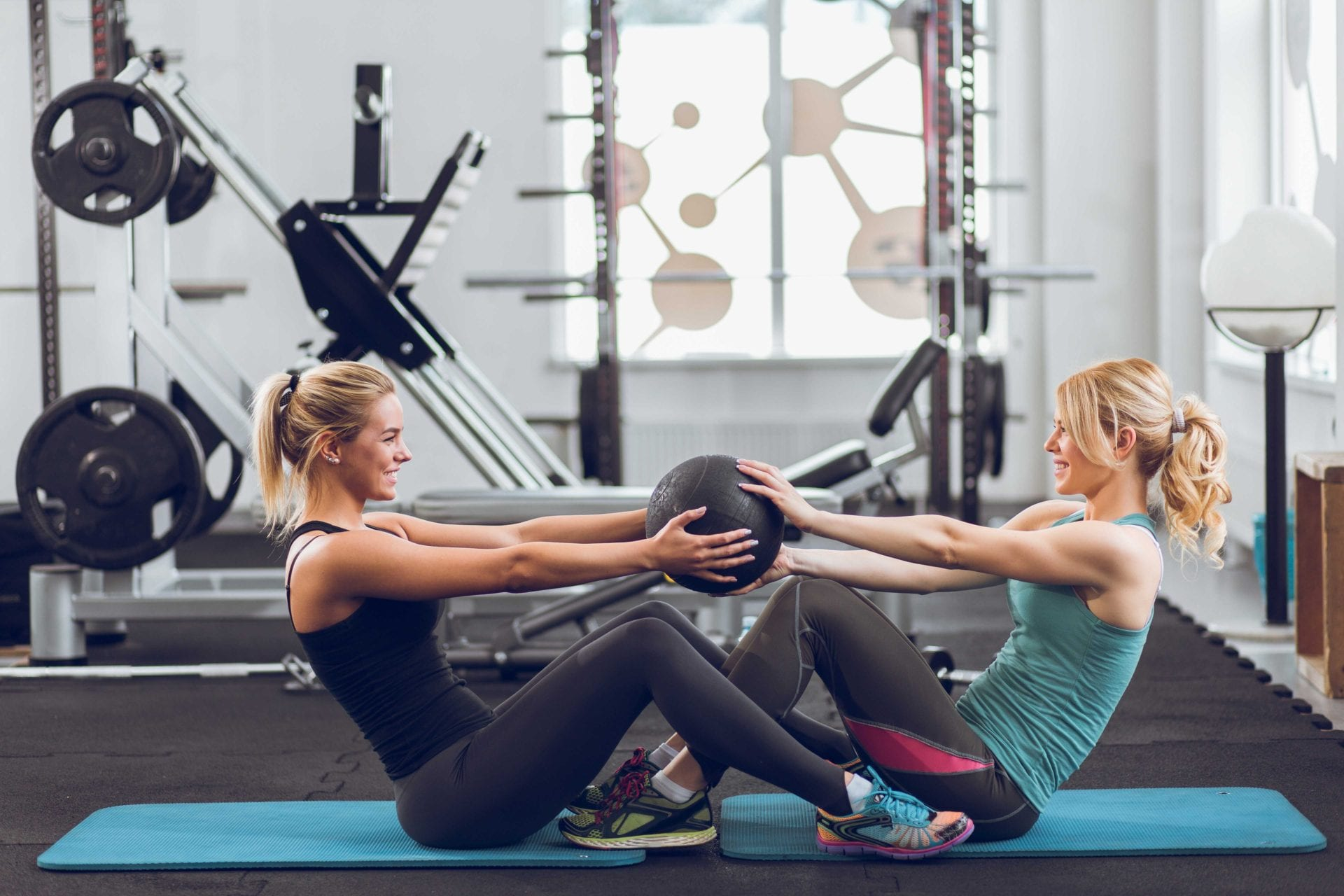 Young sporty women doing doing sit-ups with medicine ball