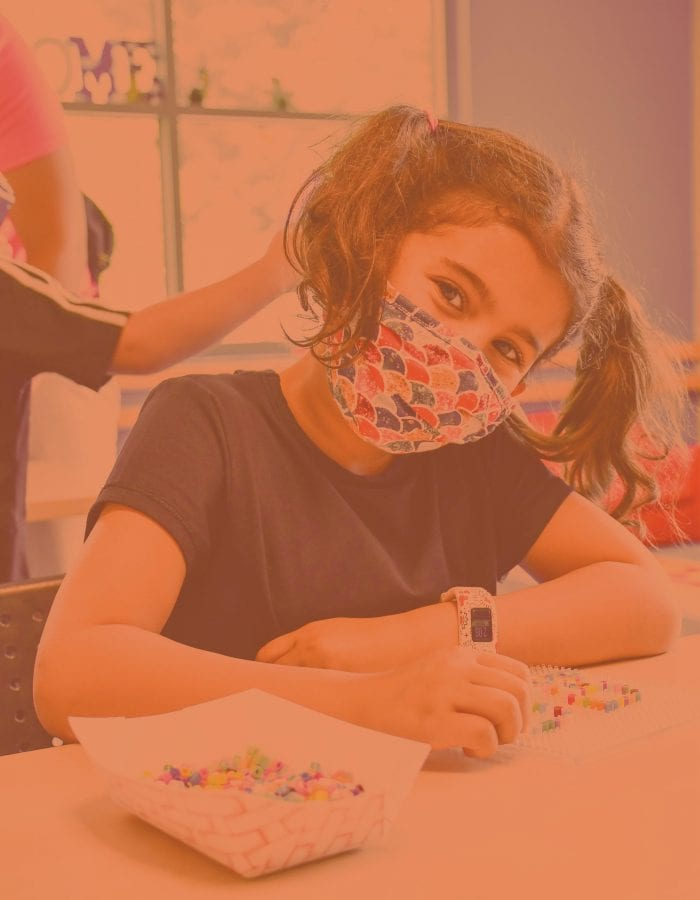 Girl wearing mask at desk