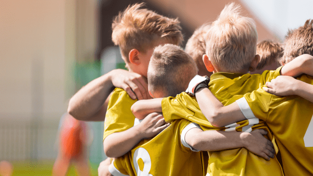 Kids in a huddle playing sports