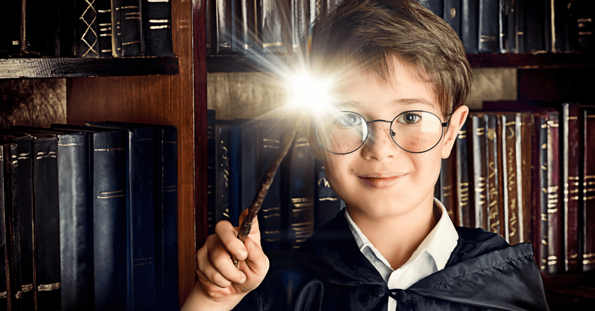 A child holding a wand during magic and muggles week